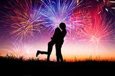 Loving young couple with fireworks background — Stock fotografie