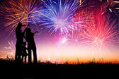 Happy family standing on the hill and watching the fireworks — Stock Photo