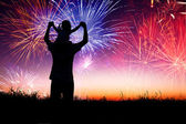 Father with child standing on the hill and watching the firework — Stock Photo