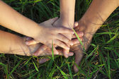 Family hand stack together on the grass — Stock Photo