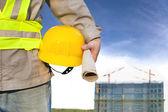 建設労働者の帽子を保持するいると建築 — ストック写真
