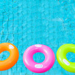 Three colorful swimming pool rings on the water — Stock Photo #27328383