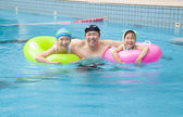 Happy family in the swimming pool — Stock Photo