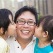 Happy little girls kissing their father — Stockfoto