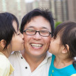 Happy little girls kissing their father — Stock Photo