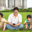 Happy family using smart phone and tablet pc outdoor — Stock Photo