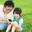 Happy father and little girl watching the smart phone — Stock Photo