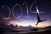 Happy new year 2014.young man jumping and drawing 2014 by flashl — Stock Photo