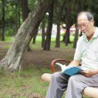 Happy senior man sitting on  bench and reading  book — Stock Photo