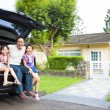 Happy family sitting in the car and their house behind — ストック写真
