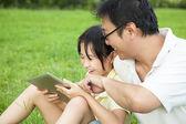 Ojciec uczy dziewczynki za pomocą komputera typu tablet — Zdjęcie stockowe