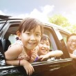 Happy little girl with family sitting in the car  — Stock Photo