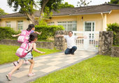 Happy father with kids in front of house — Stock Photo