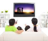 Family watching the tv in living room — Stok fotoğraf