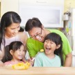 Happy family and daughter eating fruits in the kitchen — Stock Photo