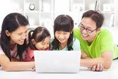 Familia con niños mirando portátil — Foto de Stock