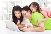 Happy family with child looking at laptop — 图库照片