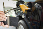Man counting money with gasoline refueling car at fuel station — Stock Photo
