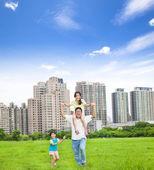 Família feliz correndo no parque da cidade — Fotografia Stock