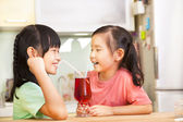 Two little girls drinking juice at home — Stock Photo