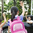 Постер, плакат: Little girls say good bye with father in front of school