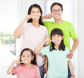 Happy family brushing their teeth — 图库照片