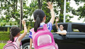 Little girls say good bye with father in front of school — Stock Photo