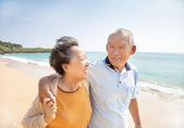 Happy asian seniors walking on the beach — Stock Photo
