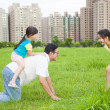 Happy  father playing with daughters in the city park — Stock Photo