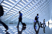 Motion blurred commuters At the airport — Stock Photo