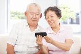 Happy seniors watching the smart phone — Stock Photo
