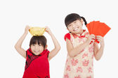 Happy kids showing red envelope and gold for chinese new year — Stock Photo