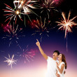 Happy young couple watching the fireworks in the sky — Stock Photo