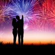Young couple standing on the hill and watching the fireworks — Foto Stock