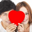 Smiling couple holding the love sign — Stock Photo