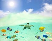 Happy young man swimming undersea with colorful fishes and bubbl — Stock Photo