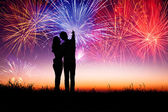 Young couple standing on the hill and watching the fireworks — Stock Photo