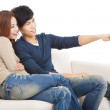 Young couple on sofa watching TV with remote control — Stock Photo