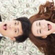 Surprised businessman and woman lying on the money — Stockfoto