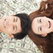 Happy businessman and woman lying on the money — Stock Photo