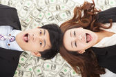 Surprised businessman and woman lying on the money — Stock Photo