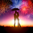 Couple kissing under umbrella with firework in the sky — Stock Photo