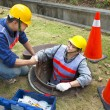 Stock Photo: Two sewerage workers in the manhole