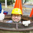 Sewerage worker in manhole with thumb up — Stock Photo #37408975
