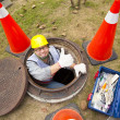 Stock Photo: Sewerage worker in manhole with thumb up