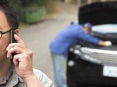 Man Talking on Phone While Mechanic Fixes Car — Stock Photo