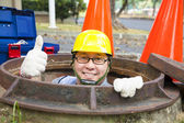 Sewerage worker in the manhole with thumb up — Stock Photo