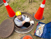 Sewerage worker in the manhole with thumb up — Foto Stock