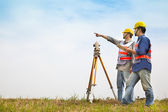 Surveyor engineer making measure with partner on the field — Stock Photo