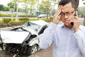 Upset driver talking on mobile phone with crash car — Stock Photo